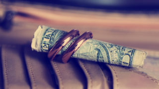 Gold wedding rings so close and a dollar, love and money